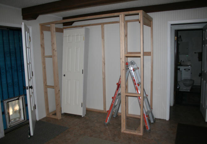Front And Back Frame Attached At The Top. Front Frame Against Wall,  Attached To Wall. Framing Of Door Area Started.